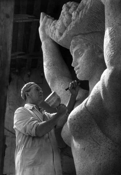 A sculptor carving a huge stone statue of a Classical style female figure. Date: 1930s