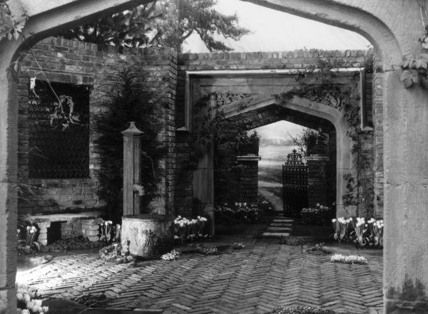 An old water pump and block paved entrance, through a lovely arched wrought iron gateway into a secret garden or suchlike... Date: 1930s