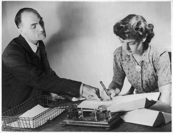 A man runs through a document with his secretary and together they edit it - he points out the mistakes and she writes in the corrections