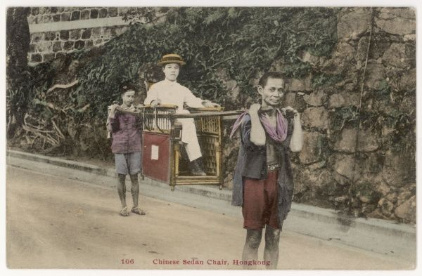 A young lady is carried through the streets of Hong Kong by two men bearing her in a sedan chair