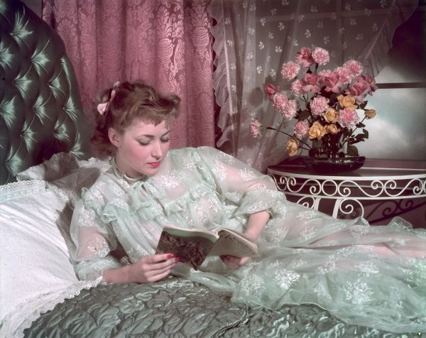A woman wearing a pale blue transparent neglige with floral motifs, yoke & long sleeves, relaxes with the 'Readers Digest' on a satin, quilted bedspread