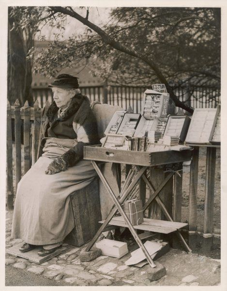 An old woman sells chocolate on the street in Kensington, London, including Mars Bars, Milky Way and tubes of Rolo