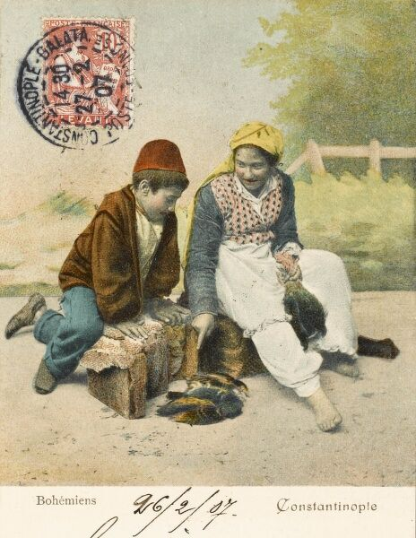 Young Turkish girl selling small fowl with her brother, whom she is instructing in the finer points of street-based avian commerce