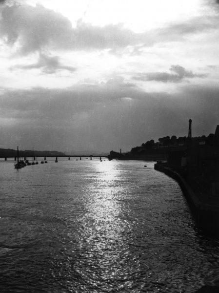 A September sunset over Teignmouth, Devon, England, looking westwards up the River Teign, from the Old Quay, with Shaldon Bridge in the distance. Date: 1950s