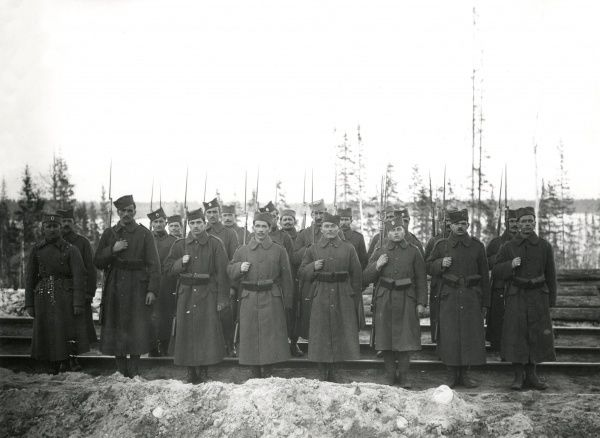 A Serbian detachment standing to attention on the railway siding at Nadvoitsa (Nadvoitsy), Murmansk, during the Russian Civil War. Date: 1919