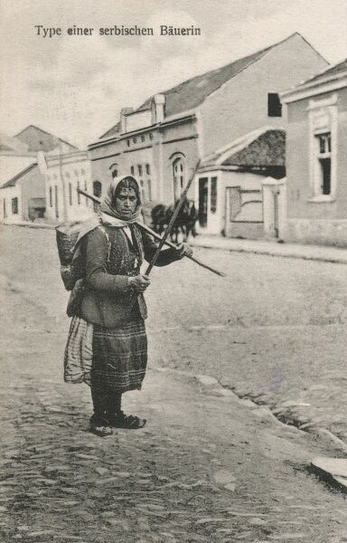 A Serbian Worker with backpack and sticks, standing on the cobbled apavement of a provincial town