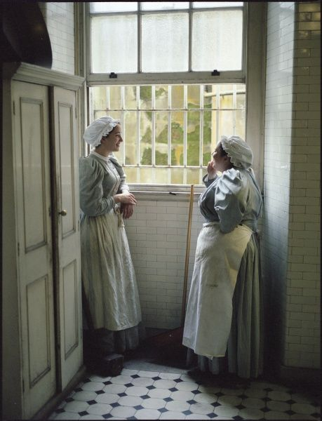 A kitchen maid and a scullery maid share a well-earned rest and chat at the window of the basement kitchen in an Edwardian country house