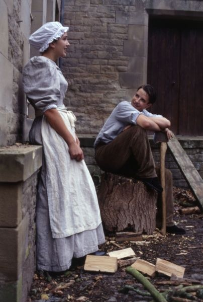 An Edwardian Scullery Maid falls for the Hall Boy as he chops firewood. Date: early 1900s (re-enactment)