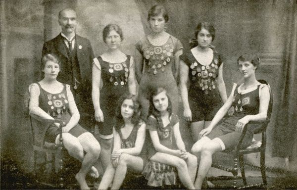 Seven young lady swimmers, five of them with several medals pinned to their costumes