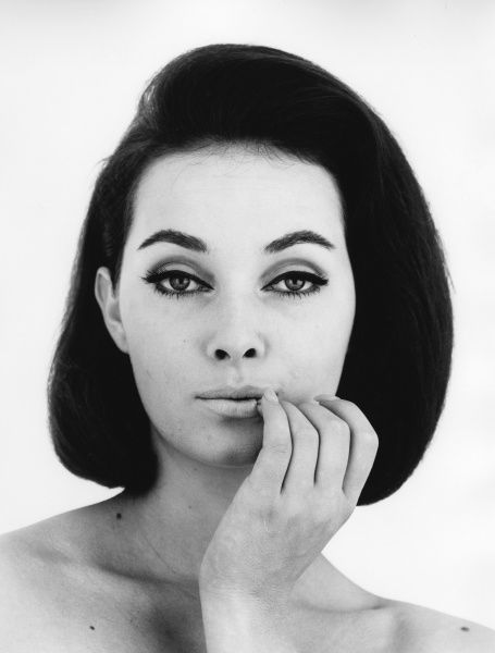 Head and shoulders portrait of a dark haired woman who appears to be topless. She's touching her lips with her finger tips