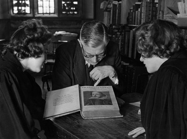 A professor and two graduate students look at Shakespeare's first folio in the library of Durham University. Date: 1950s