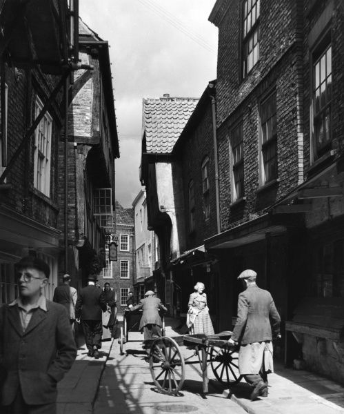 The Shambles, York, with two old workmen in flat caps pushing carts and a typical schoolboy wearing a school cap and spectacles, on the front left of the picture. Date: 1950s