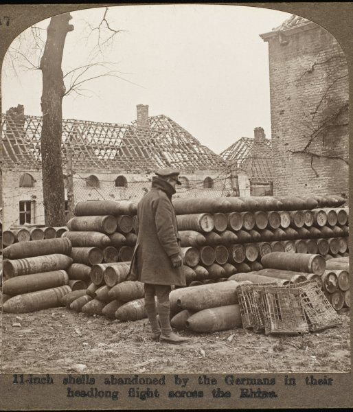 A British soldier inspects a large haul of shells abandoned by the Germans near Cambrai during the offensive of 1917. Roofless houses provide a poignant backdrop