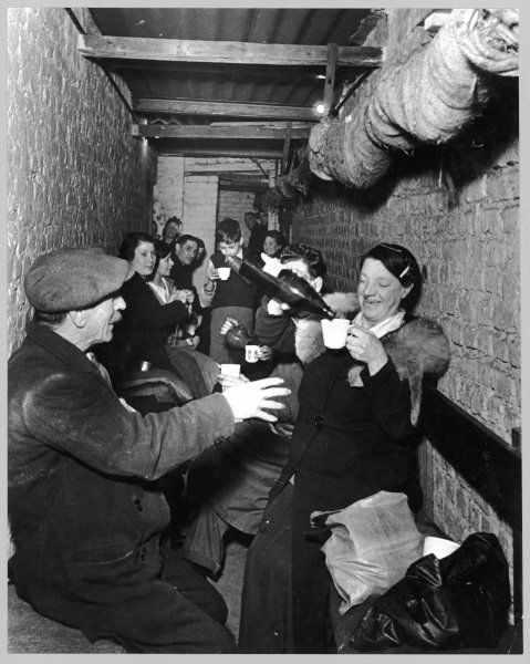 Sheltering underground during The Blitz, Islington, London; a woman pours drinks for those around her