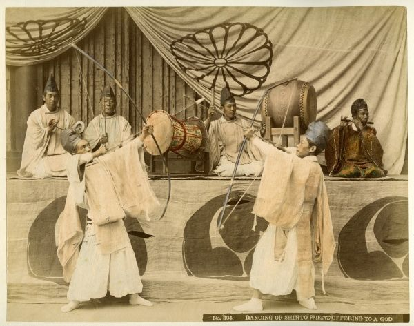 Shinto priests perform an elaborate dance in offering to a god; the symbol on the drapery is the Imperial Seal of Japan