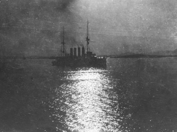 A ship with four funnels at sea by night, with light reflecting on the water, during the First World War