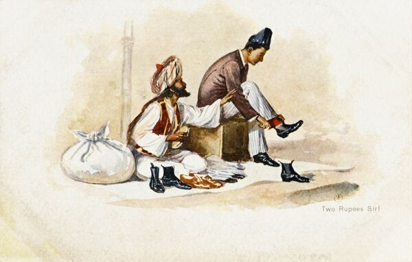 A shoe shiner demands the payment of two rupees for the fine job he has done to buff up a fine shine in his clients pait of smart black shoes at his streetside stall