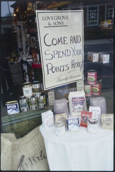 A window display at 'Lovegrove & Sons' family grocers, inviting people to 'Come and Spend Your Points Here', i.e. to use up their rationing coupon points during wartime