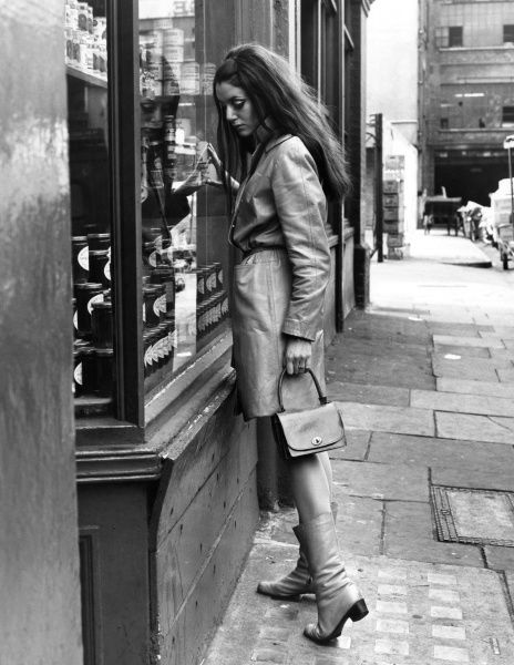 A woman looks at a can of food through a shop window. Date: late 1960s