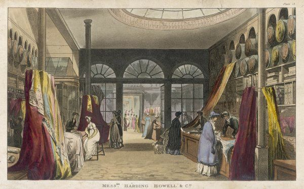 A throng of mostly feminine customers scrutinize the stock at Messrs. Harding, Howell & Co. at 89 Pall Mall. Fabrics cascade from displays in the drapery department