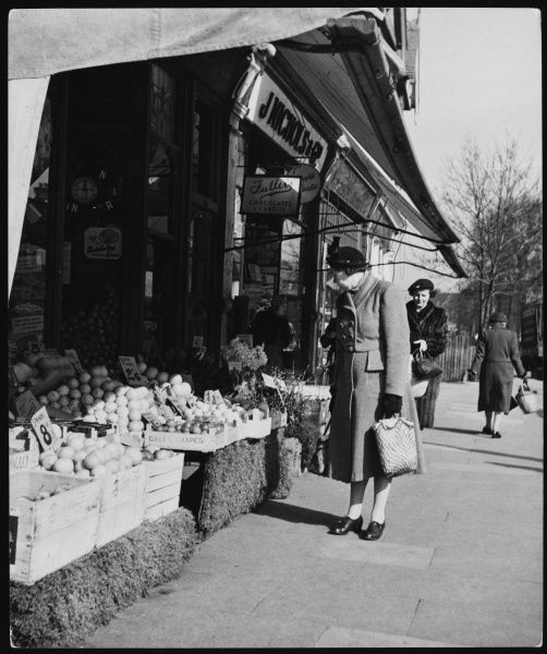 Ladies in hats and coats shop in Cranbrook Road, Ilford, Essex; the greengrocer's shop has a fine display of fruit and vegetables outside in crates, prices in shillings