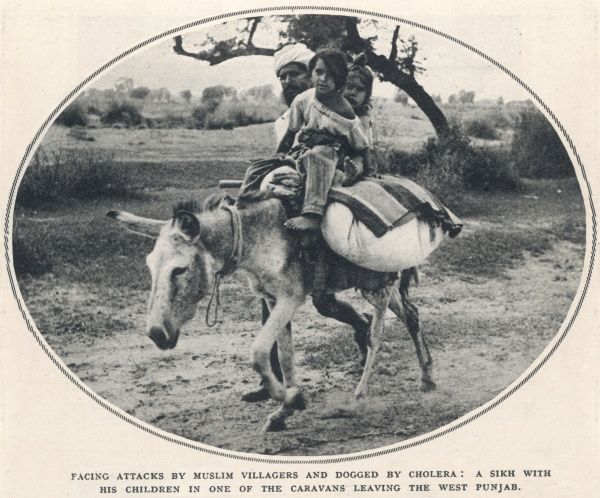 A Sikh man with his children in one of the caravans leaving the West Punjab region for the comparative safety of the East Punjab. Such caravans were under constant threat of attack by Muslin villagers and outbreaks of Cholera
