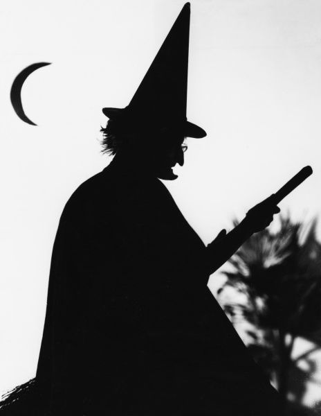 A silhouette of a witch with her broom and a new moon. She has a particularly pointed nose and chin