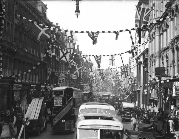 Central London, heaving with buses and traffic, gaily decorated with flags and bunting to celebrate the Silver Jubilee of George V and Queen Mary