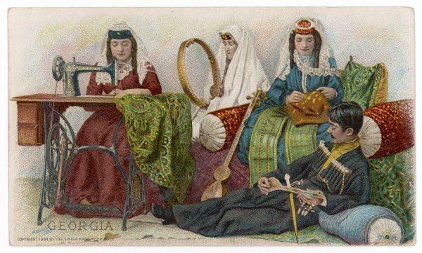 A woman of Georgia uses her Singer machine while her companions use traditional methods and a handsome young man provides a musical accompaniment