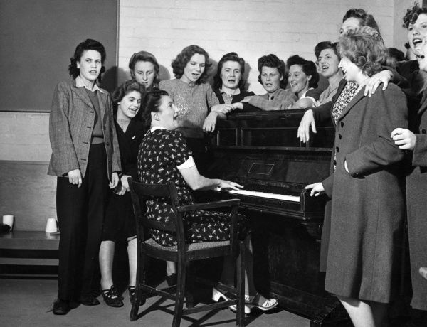 A group of women, possibly actresses or chorus girls, gather around a piano in what looks like a rehearsal room to sing their hearts out