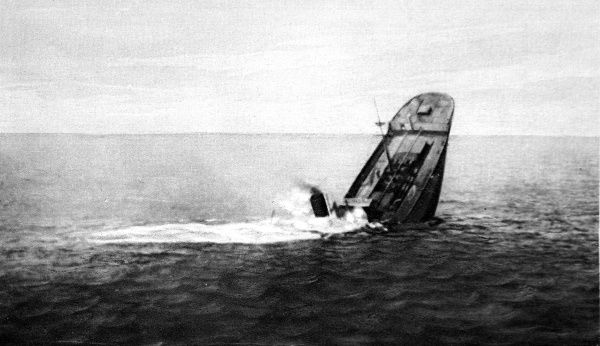 Photograph showing a sinking British Merchant ship, after she had been torpedoed by a German submarine, 1916. In this picture the ships funnel has reached the waterline and the stern is lifted into the air as she sinks, bows first