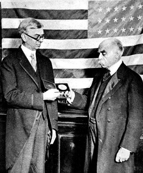 Photograph showing the American Ambassador to Great Britain, Mr. Harvey (on left), presenting an American Geographical Society Medal to Sir Francis Younghusband; London, 1922. Sir Francis Edward Younghusband (1863-1942)was a leading British explorer