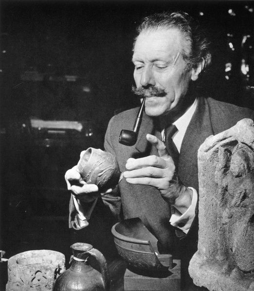 Portrait of Sir Mortimer Wheeler (1890 - 1976), archaeologist and broadcaster, seated at his desk in the British Academy