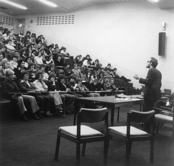 View of a sixth form lecture theatre, with the male lecturer speaking to a full audience of students. Date: 1967