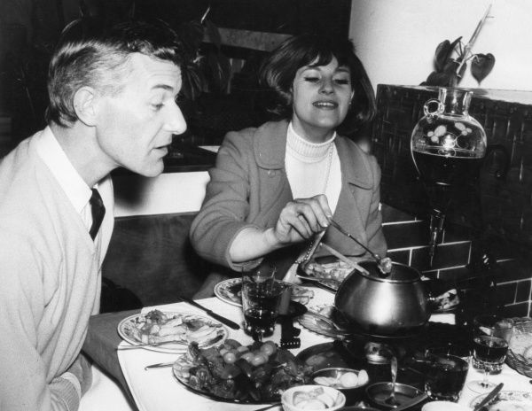'Urgh - what's that?' A young husband strains to see what his experimental wife has conconcted for their evening meal! Date: 1960s