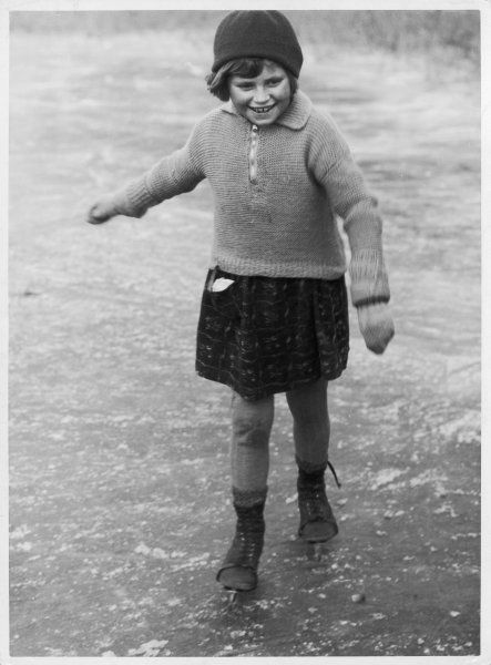 Girl in her winter woollies wears a hat, gloves, stockings & hand-knitted jumper in garter stitch with zip fastening & collar. The skirt of her dress is rather short