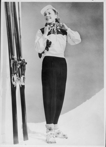Skiing Suit with a wind-proof jacket with lace-up front & contrasting yoke by Jean Destre. The model also wears a hat with a visor