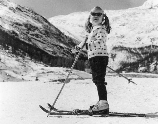 A little girl with her hair in pigtails, learning how to ski. Date: 1960s