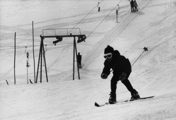 A skier with a ski lift behind him, Switzerland.  1960s