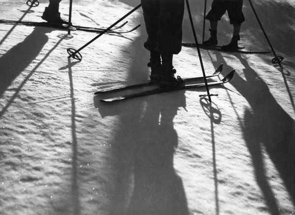 Skiers, skis and ski poles cast artistic shadows across the snow. Date: 1930s