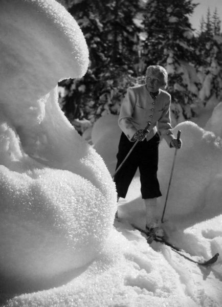 A blonde skier gingerly negotiates a large snow drift, hoping to avoid an avalanche! Date: 1930s