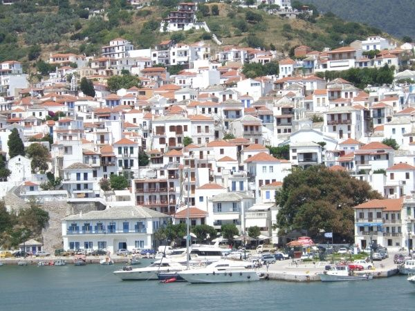 White painted housed with red tile roofs cling to the hillside town of Skopelos Town, Skopelos, one of the Sporades group of islands, of Greece