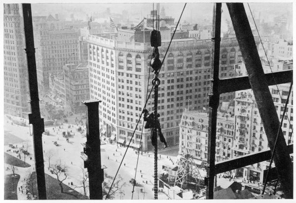 A man hangs precariously from a line during the construction of a skyscraper in New York