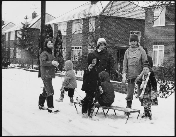 Mothers and children playing with a sledge in the snow on a suburban street in Horley, Surrey, England