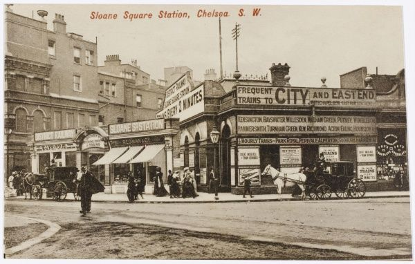 A street scene outside Sloane Square Underground station in Chelsea, London, with frequent trains to the City on the District Railway