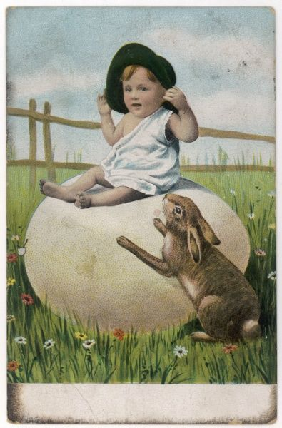 A small boy sits on a large Easter egg in a spring meadow, while the March Hare looks up at him