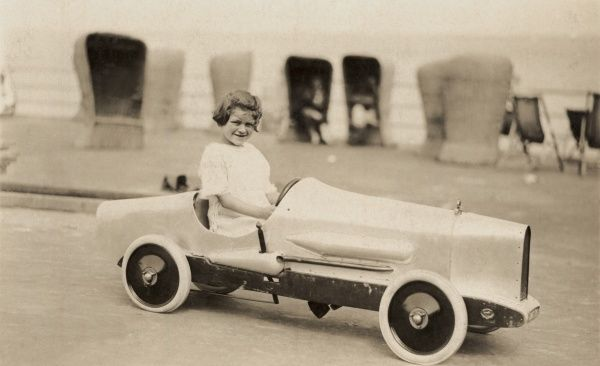 A little girl grins for the camera as she poses in a sleek and speedy looking pedal sports car somewhere close to the sea, as evidenced by the deckchairs in the background, lining the promenade