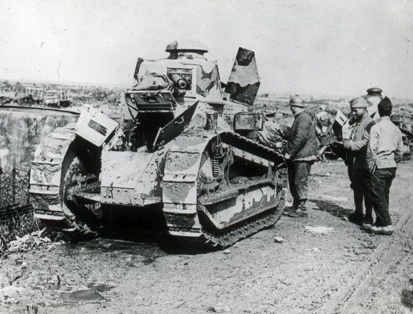 A small tank on a country road, undergoing maintenance during the First World War