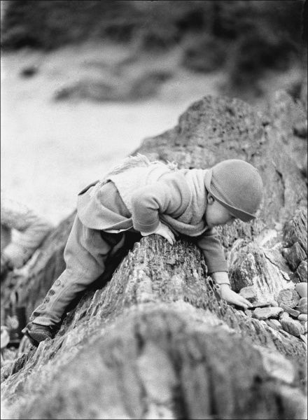 A young boy playing on a rocky outcrop on a beach in Devon. Photograph by Ralph Ponsonby Watts