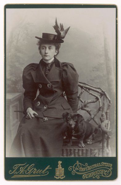 A smart young woman wearing a dark suit with 'mutton chop' sleeves, photographed with her favourite dachshund